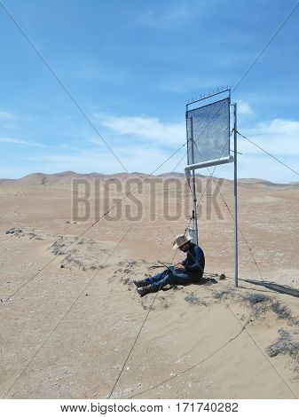 PATACHE CHILE 12 JANUARY 2017: scientist with laptop sitting and working under experimental climatological installation outdoors in a desert
