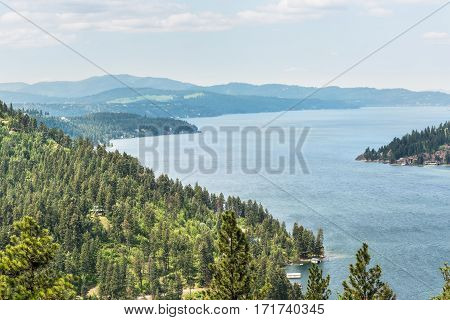 View of Coeur d'Alene lake from mountains with pine trees in Idaho