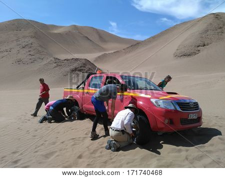 PATACHE CHILE 12 JANUARY 2017: people trying to dig out 4x4 which stuck in the sand