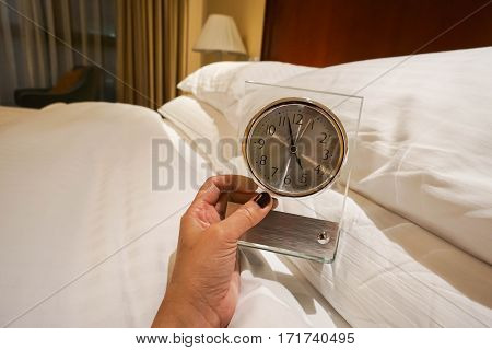 woman hold clock for alarm setting in bedroom