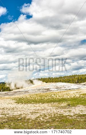 Old Faithful Geyser waiting to erupt in Yellowstone National Park with steam and clouds