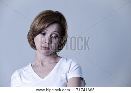 head and shoulders portrait of young beautiful woman on her 30s sad and depressed looking low and tormented feeling worried suffering breakdown isolated background in depression emotion