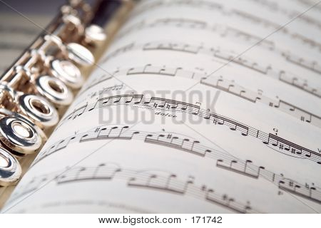 A Flute Rests Inside A Musical Score