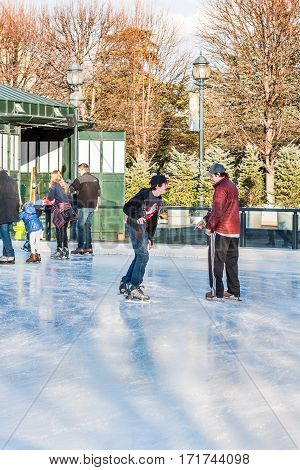 Washington DC, USA - January 28, 2017: Two young men skating in ice rink in National Gallery of Art Sculpture garden