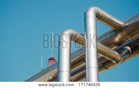 Gas pipelines reflect against clear blue sky