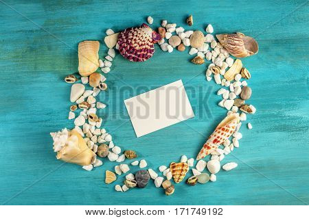 An overhead photo of sea shells and pebbles forming a frame on a vibrant turquoise background, with a business card inside. A design template for a summer vacation banner