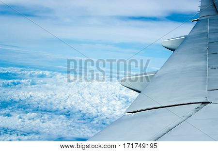 Aircraft wing on the clouds flying background