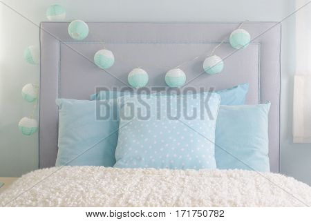 Light Blue Pillows Setting On Bed With Decorative Ball On Headboard