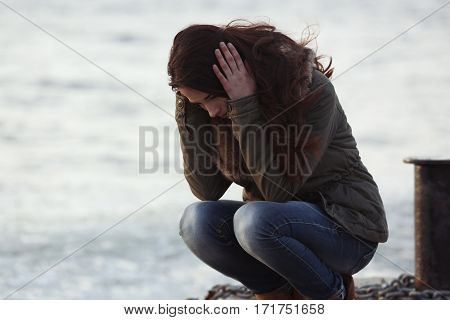 Depressed young woman on pier