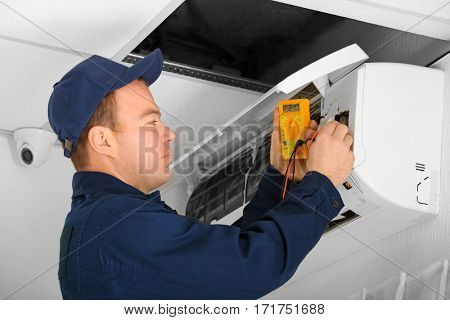 Electrician measuring voltage of air conditioner in office