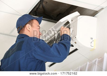 Worker carrying out maintenance of air conditioner in office