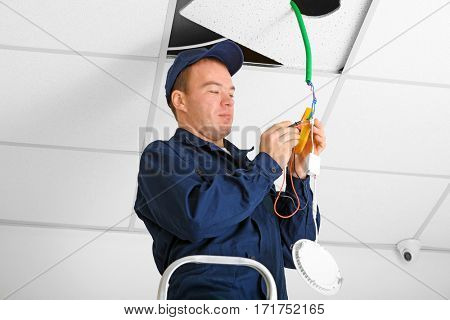 Electrician checking voltage in office