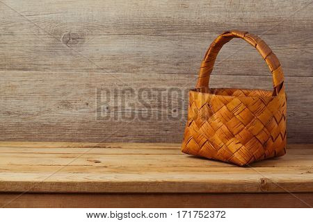 Picnic basket tablecloth on wooden table over rustic background