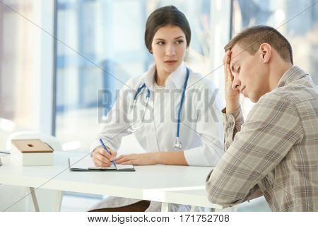 Young depressed man at doctor's office