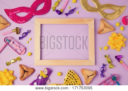 Purim holiday concept with wooden frame carnival mask and hamans ears cookies on purple background. Top view from above. Flat lay