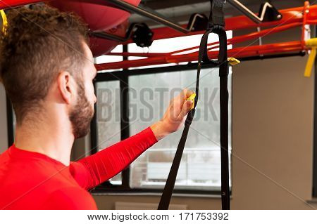 young sporty bearded man prepares for exersising in gym Adjust the length of the sling straps
