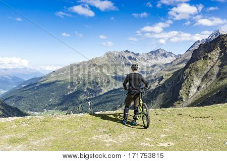 Mountain biker with protection gear and bike stands on the edge of a mountain platform and enjoys the view of the alps before riding downhill.