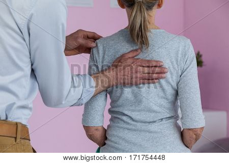 Physiotherapist giving back massage to female patient in clinic