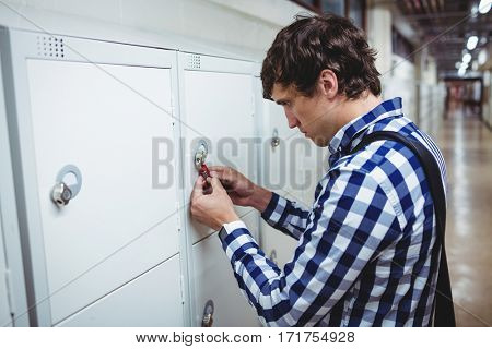 Student opening his locker in college