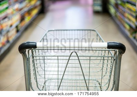Empty shopping cart in grocery section of supermarket