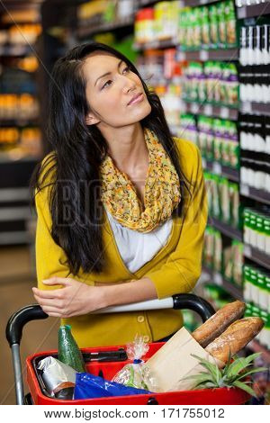 Thoughtful woman standing with shopping cart in grocery section of supermarket