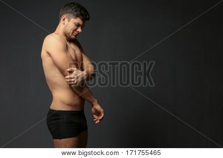 Young man suffering from pain in elbow on dark background