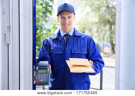 Courier holding packages and payment terminal in doorway