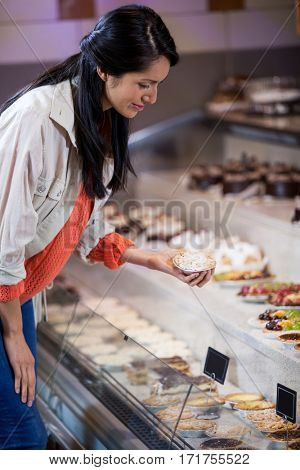 Woman selecting dessert from display in supermarket