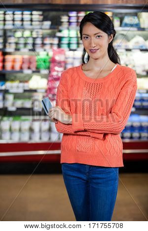 Portrait of smiling woman holding credit card in grocery section of supermarket