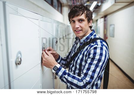 Portrait of smiling student opening his locker in college