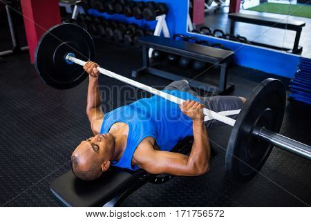 High angle view of male athlete doing bench press in fitness studio
