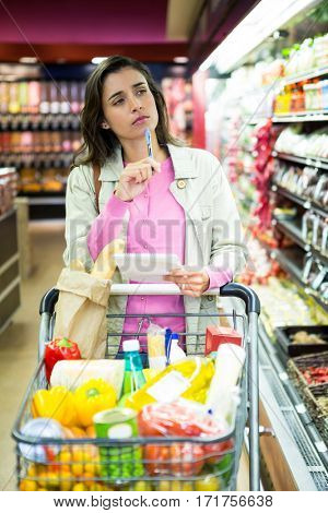 Woman with notepad shopping for vegetables in grocery section at supermarket