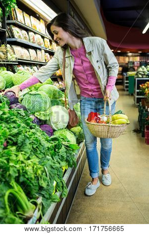 Woman with wicker basket buying vegetables in organic shop at super market