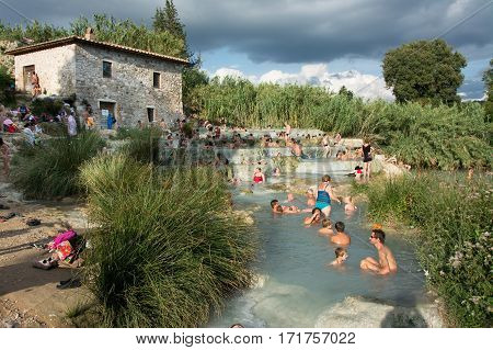 SATURNIA ITALY - August 24 2015: tourists swimming and relaxing in hot springs in Saturnia at Mulino this spa world famous has natural waterfalls near the city of Manciano in tuscan