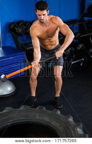 Full length of shirtless man exercising with sledgehammer in gym