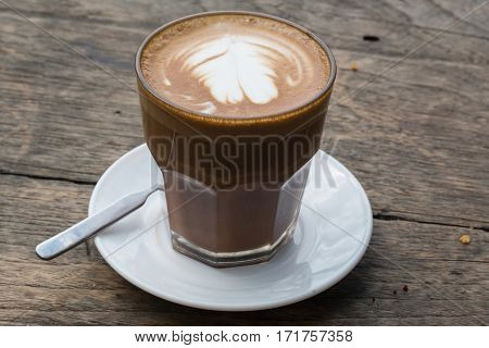 the coffee cup on wooden table background