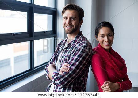 Portrait of happy colleagues standing back to back by window in office