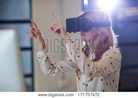 Young woman wearing virtual reality glass in office