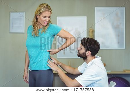 Physiotherapist examining womans back in clinic