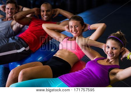 Portrait of smiling friends with hands behind back while stretching in gym