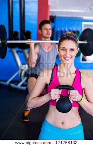 Portrait of smiling woman holding kettlebell with man lifting weights in gym