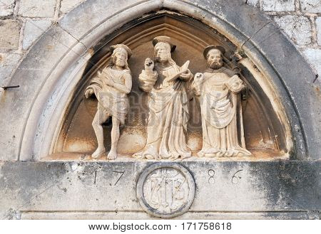 DUBROVNIK, CROATIA - NOVEMBER 30: Jesus Christ, St. John the Baptist and St. Nicholas with a stick, portal of Saint Luke Church in Dubrovnik, Croatia on November 30, 2015.