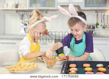 Cute little children decorating Easter cookies at kitchen