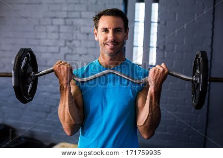 Portrait of smiling man exercising with barbell in fitness studio