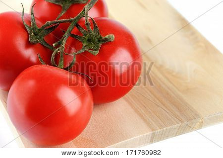 The branch of cherry tomatoes on a cutting board isolated on white background. Soft selective focus and shallow depth of field