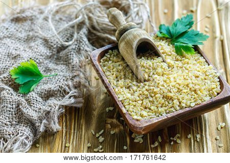 Bulgur And Scoop In A Square Wooden Bowl.