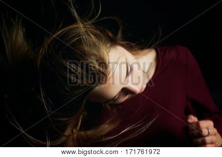 The hand in her hair. Beautiful young girl dancing. Hair flying. Shooting in Studio