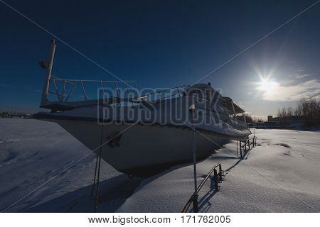 Frozen ship staying on river covered ice at winter sunny day, wide angle