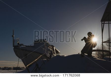 Photographer travelers concept. Russian ice harbor near vessel at sunny day, silhouette