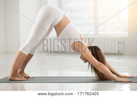 Young attractive yogi woman practicing yoga, doing Downward facing dog exercise, adho mukha svanasana pose, working out wearing sportswear, sport bra, pants, full length, white color room background